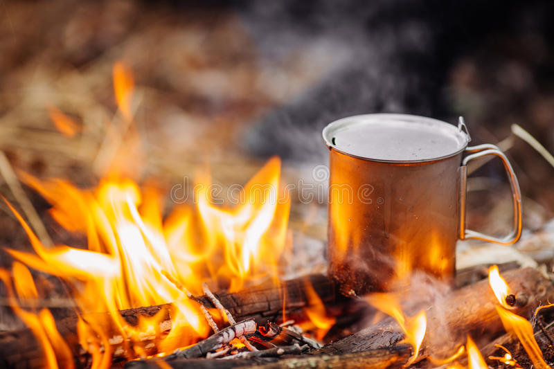Travel titanium cup on wood on forest background. Lunch during t. He journey to the wild. Camping lifestyle stock photo