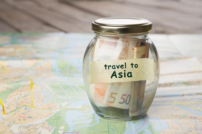 Travel to Asia - money jar and map. Travel to Asia - car key and roadmap rental sale driving insure buy alarm vehicle service business open system insurance stock image