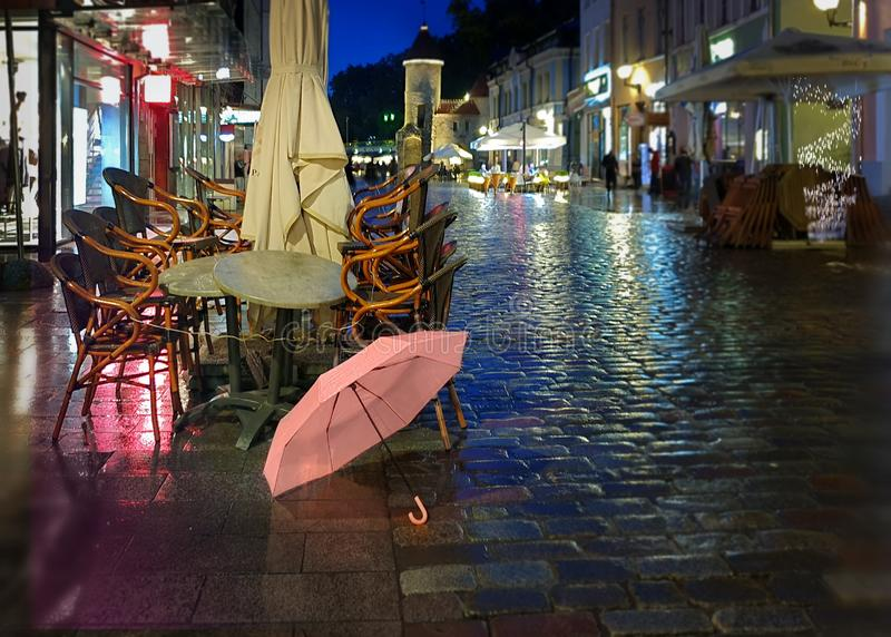 Travel to Europe Street cafe pink umbrella on old pavement  rainy evening city light    blurring bokeh effect background. Travel to europe ,Street cafe night royalty free stock images