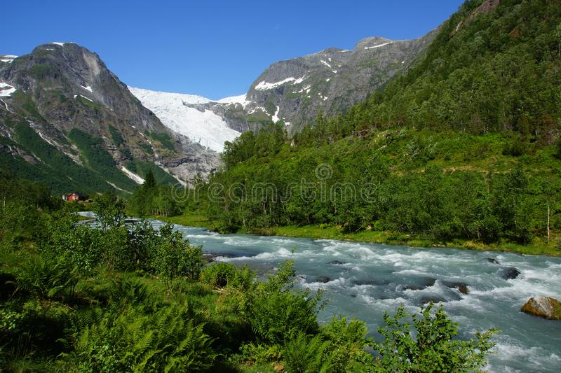 Travel to Norway, the blue mountain river flows among stones and bushes from a high mountain with a glacier royalty free stock photography
