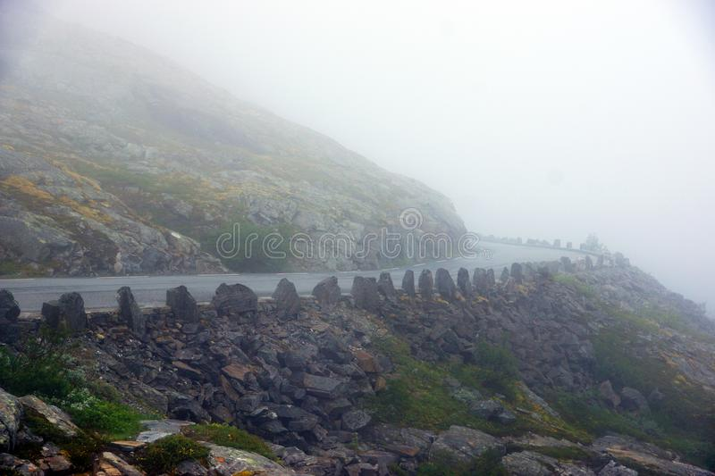 Travel to Norway, heavy fog on a mountain road turning left stock images