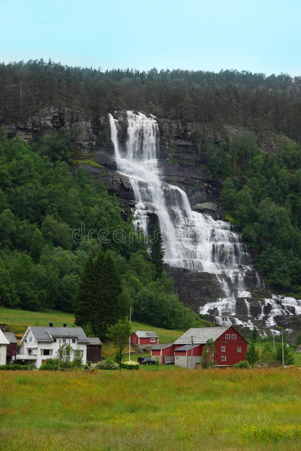 Travel to Norway, a large waterfall flows down from the mountain, near a settlement of several bright houses royalty free stock photo