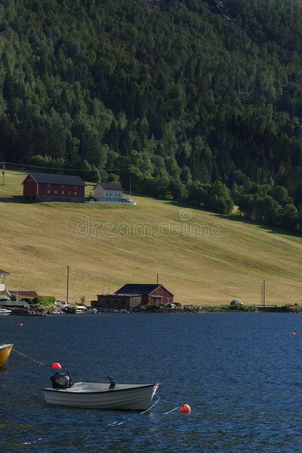 Travel to Norway, a white boat moored in the river, the opposite bank with the house and the field can be seen.  royalty free stock images