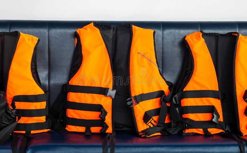 Travel to The Sea Safety. Group of Orange Life Vests on Blue Seat in Speed Boat for Tourist to use When Snorkeling in Ocean. To Explore Under Water Adventure stock photo