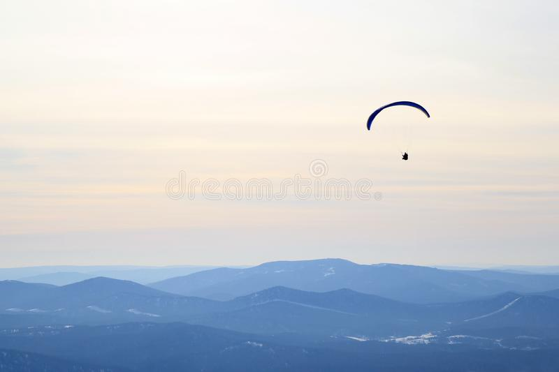 Paraglider is flying in the sky above the mountains. Winter landscape. royalty free stock images