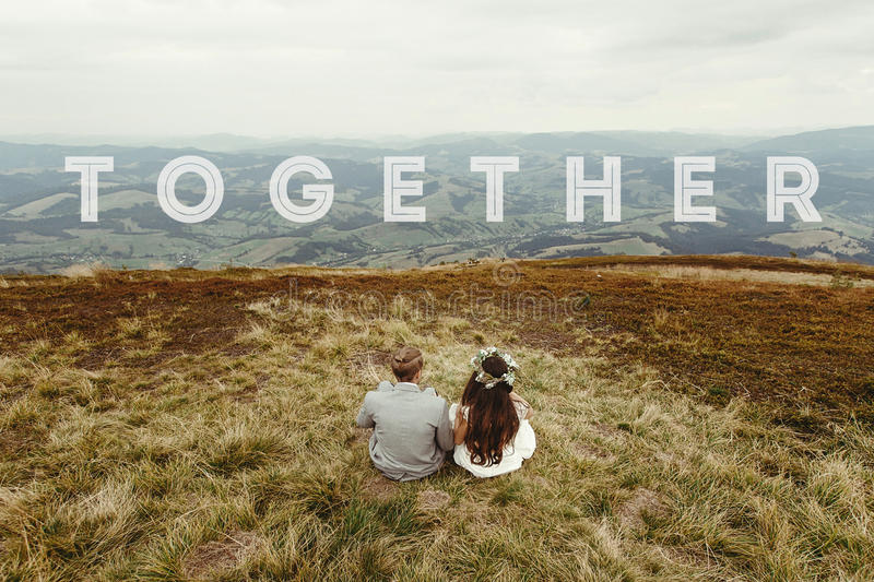 Travel together concept, text, happy gorgeous bride and groom si. Tting on top of a mountain, boho wedding couple, amazing view royalty free stock photography
