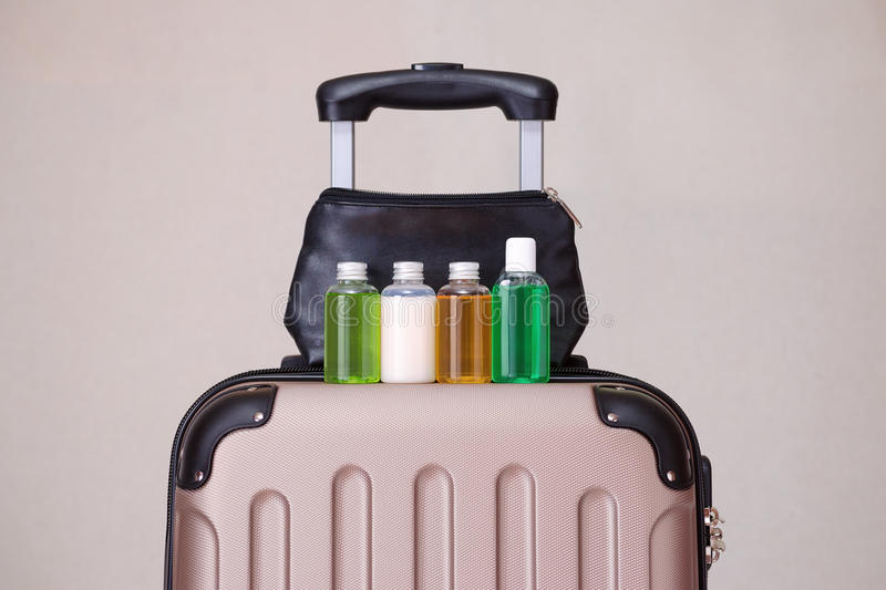 Travel toiletries, small plastic bottles of hygiene products on the suitcase. And cosmetic bag stock images