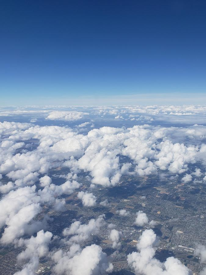 blue sky landscape with aerial view of a city between white clouds stock photos