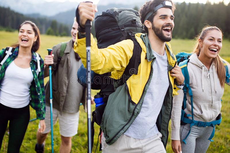 Travel, tourism, hike, gesture and people concept - group of smiling friends with backpacks stock photo