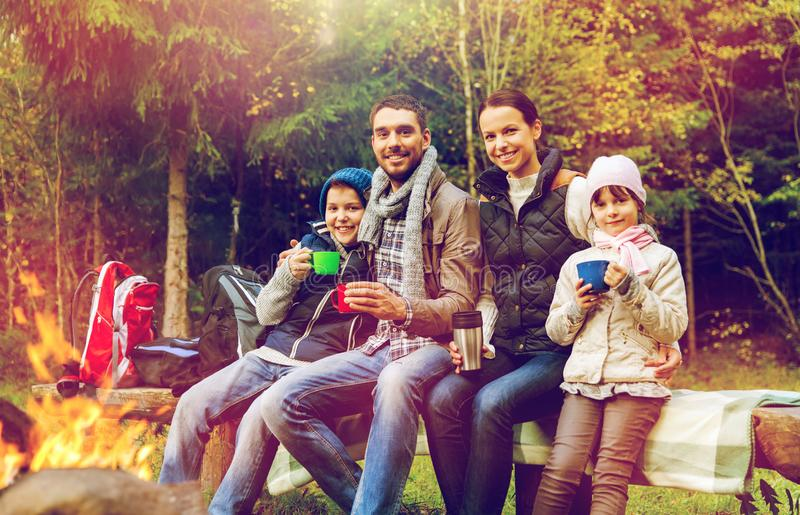 Happy family drinking hot tea at camp fire stock photography