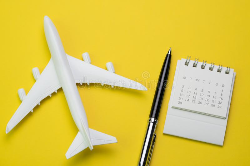Travel, tourism, holiday or vacation planning concept, small white clean calendar with black pen and toy airplane on vibrant yell. Ow background royalty free stock photography