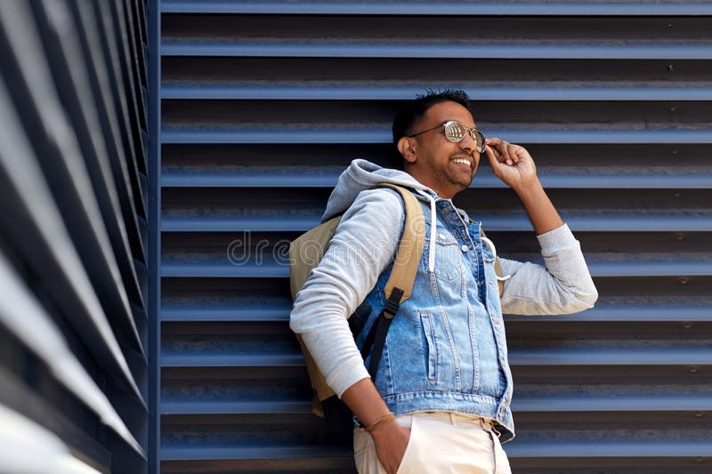 Smiling indian man with backpack on city street. Travel, tourism and lifestyle concept - smiling indian in sunglasses man with backpack on city street royalty free stock photo
