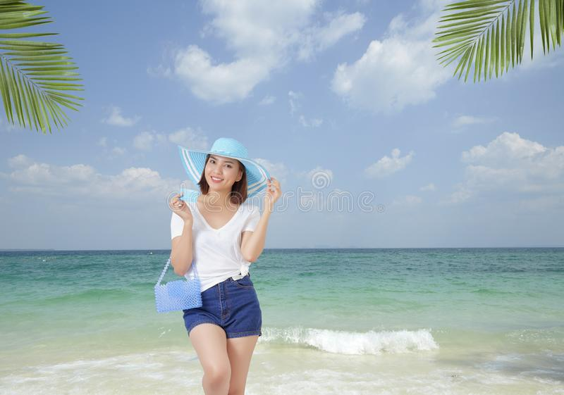 Travel, tourism and summer vacation concept - beautiful woman in hat  with holding Credit card enjoying tropical beach background royalty free stock image
