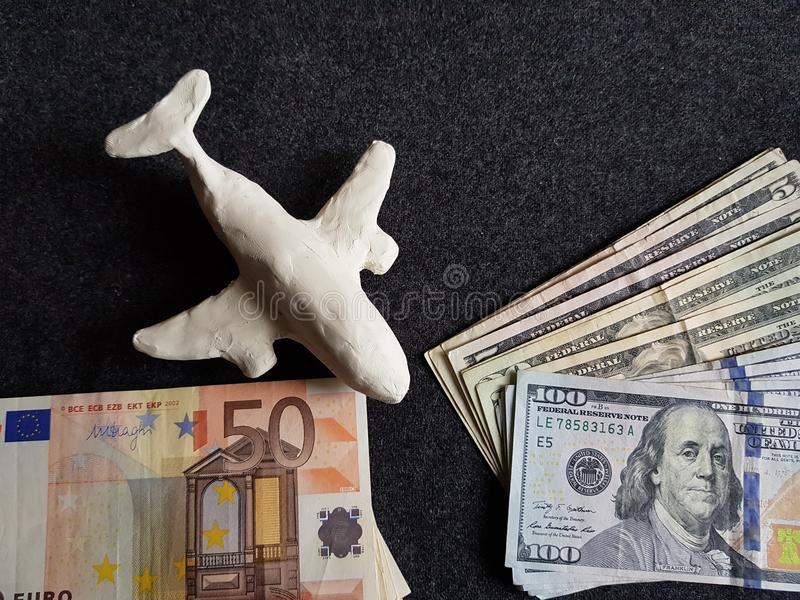 White plasticine plane, euro banknotes and dollars bills on the grey table. Travel and tourism, tax, commerce and exchange, price and offer in flight, cash and royalty free stock photography