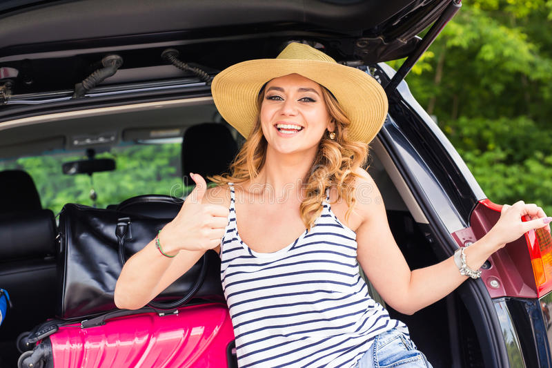 Travel, tourism - woman sitting in the trunk of a car with suitcases, showing thumb up sign, ready to leave for. Vacations stock photos