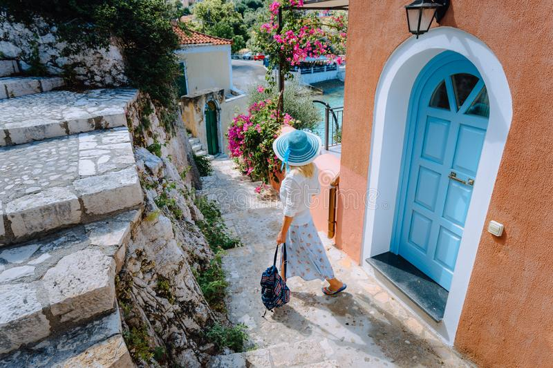 Travel tourist blonde woman with sun hat walking through narrow streets of an old greek town to the beach. Vacation stock photos