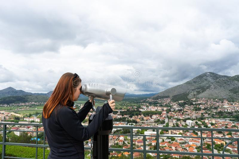Travel tourist woman on Europe holidays. Hipster girl using telescope looks panorama of the city. Travelling, leisure, recreation stock photos