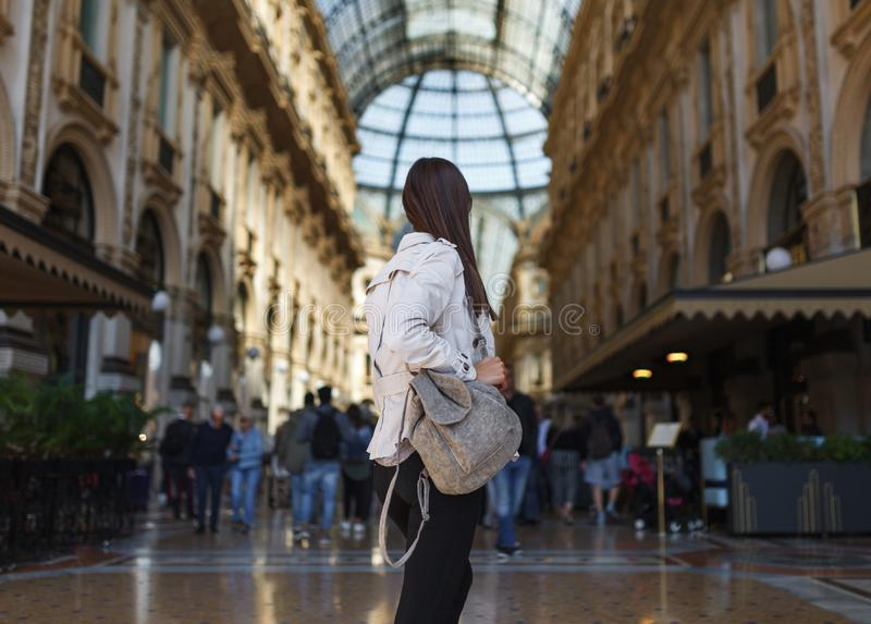 Travel tourist woman near Vittorio Emanuele gallery and Duomo di Milano - cathedral church of Milan in Italy. Blogger girl. Enjoying on the square in the city stock photo