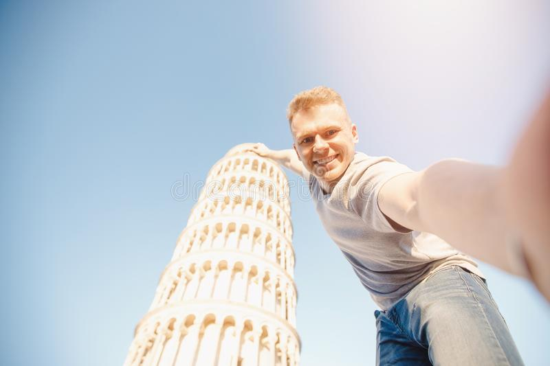 Travel tourists Man making selfie in front of leaning tower Pisa, Italy.  royalty free stock photography