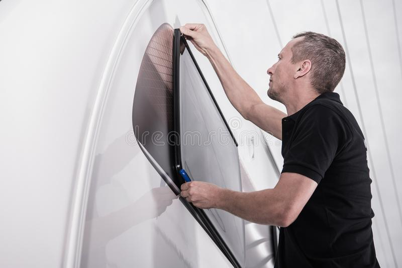 Travel Trailer Window Seal. RV Travel Trailer Window Seal Check by Recreational Vehicles Service Technician. Caucasian Worker in His 40s. Glazing Bead royalty free stock photography