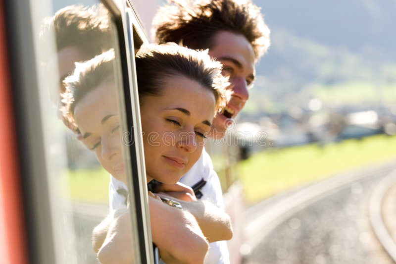 Travel by train. Photo of romantic couple looking out of train window while their travel