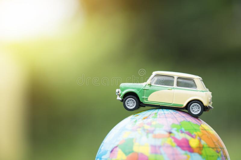 Travel and transport concept. Toy car on world map balloon. With green nature background royalty free stock photography
