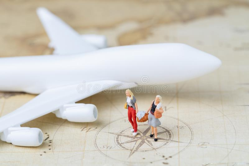 Travel or transportation concept, miniature people couple women help holding baggage walking together with toy airplane on vintage royalty free stock images