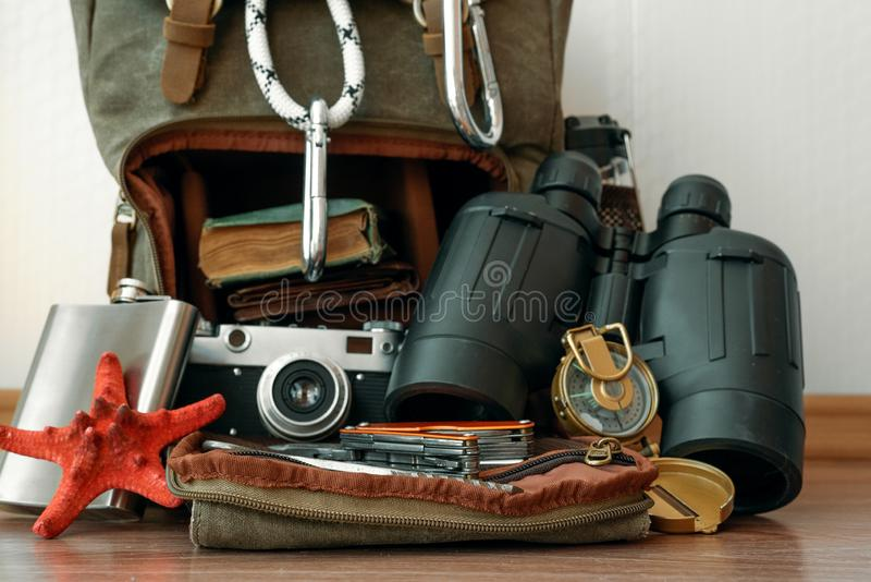 Travel. Travel or adventure background. A backpack with a safety rope with carabines, binoculars, compass, hip flask, book and photo camera on a floor on a royalty free stock images