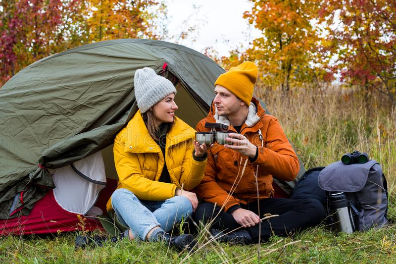 Travel, trekking and hiking concept - couple of hikers drinking tea or coffee near green tent in autumn forest royalty free stock photo