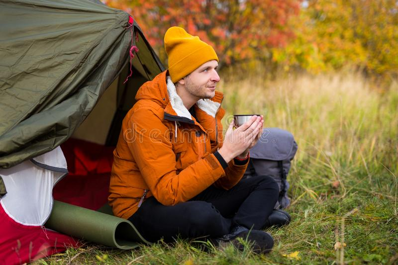 Travel, trekking and hiking concept - portrait of young man drinking tea or coffee near green tent in autumn forest stock photos