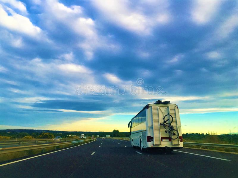 Travel, trip, tourism, adventure and camper along the way. Travel, trip, tourism, adventure, camper, bicycle, street, sunny day, clouds, nature, emotions and royalty free stock images