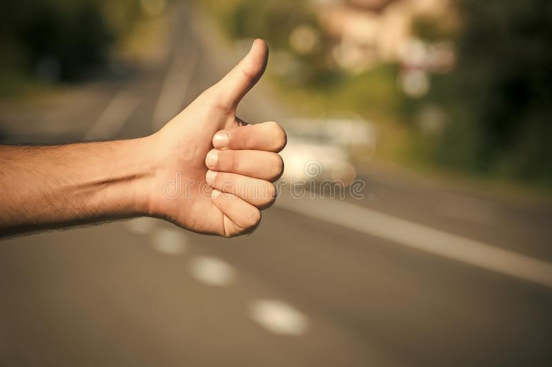 Travel, trip, vacation, wanderlust. Hitchhiking, hitching, thumbing, auto stop concept. Thumbs up male hand gesture outdoors Hitchhiker sign on road stock photo