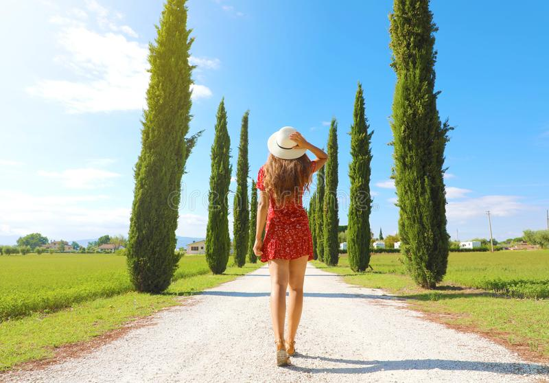 Travel in Tuscany. Young woman walking in beautiful and idyllic landscape of a lane of cypresses in the Italian countryside of stock image
