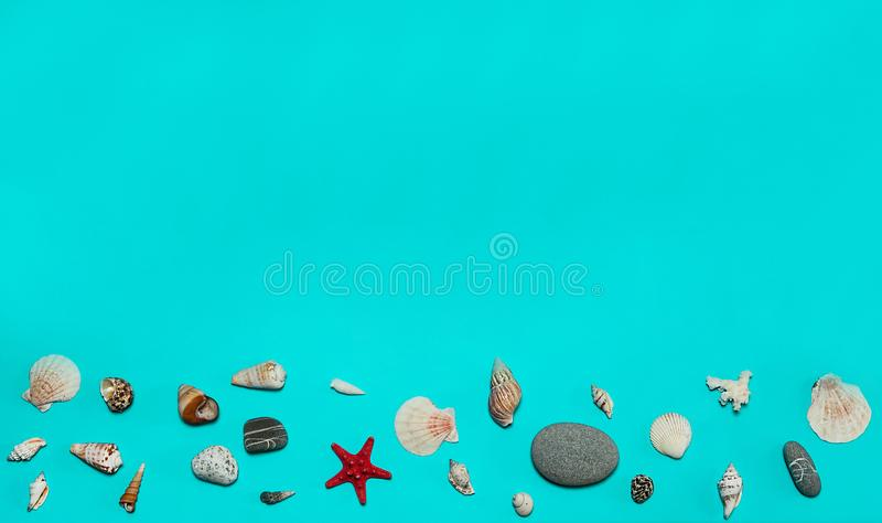 The border is made of grey sea pebbles and shells on a light blue background. stock photo