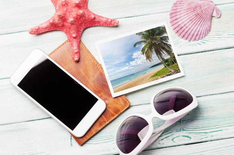 Travel vacation concept with sunglasses, smartphone and weekend photos on wooden backdrop. Top view. Flat lay. All photos taken by stock images