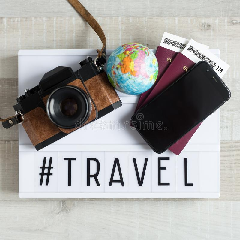 Travel and vacation concept - top view of passports, tickets, camera, smart phone and lightbox with word travel over wooden royalty free stock images