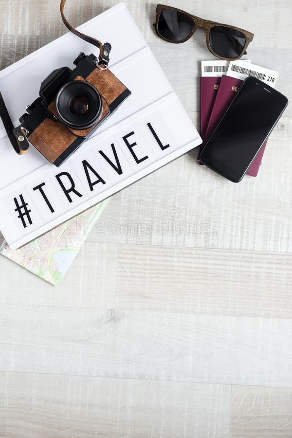 Travel and vacation concept - top view of passports, tickets, camera, sunglasses, smart phone and lightbox with word travel over stock photos