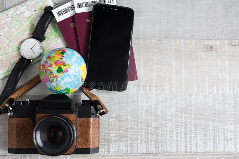 Travel and vacation concept - top view of passports, tickets, map, smart phone, wristwatch and vintage camera over wooden royalty free stock photography