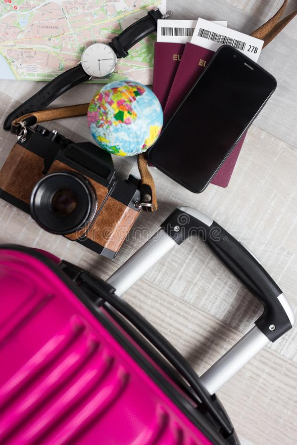 Travel and vacation concept - top view of suitcase, passports, tickets, map, smart phone, wristwatch and vintage camera royalty free stock photos