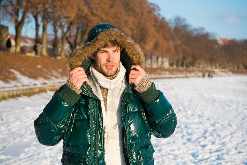 Travel and vacation concept. Winter outfit. Guy jacket hood. Man warm jacket snowy nature background. Wind resistant stock images
