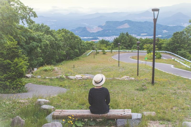 Woman wear black overcoat, She sitting on wooden bench and looking forward to Sapporo City from viewpoint of Mount Moiwa, stock photos