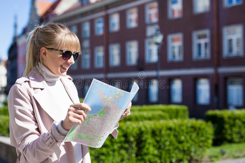 Travel and vacation concept - young woman tourist looking at the map royalty free stock photo