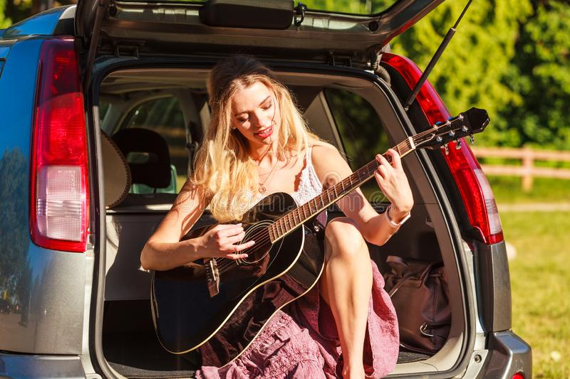 Girl with guitar on hatchback car. Travel vacation hitchhiking concept. Summer girl hippie style sitting on hatchback car with acoustic guitar stock image