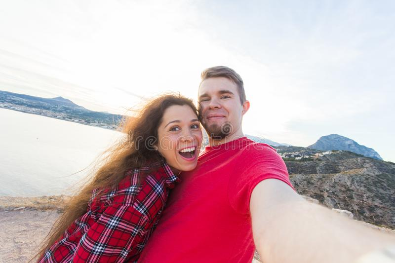 Travel, vacation and holiday concept - Beautiful couple having fun, taking selfie over beautiful landscape stock images