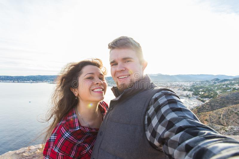 Travel, vacation and holiday concept - Happy couple taking selfie over beautiful landscape royalty free stock images
