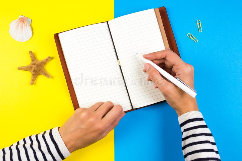 Woman hand writing in notebook over blue and yellow background stock image