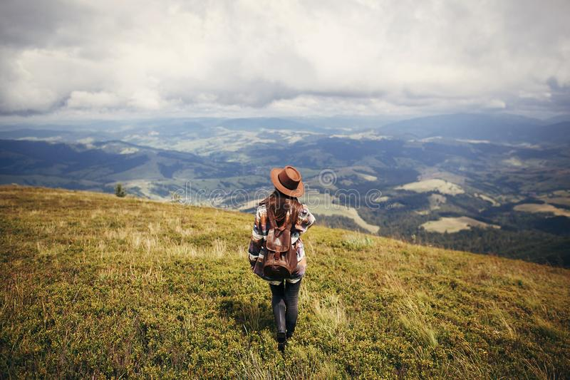 Travel and wanderlust concept. stylish traveler hipster girl holding hat, with backpack and windy hair, walking in mountains in c. Louds. summer vacation. space stock photos
