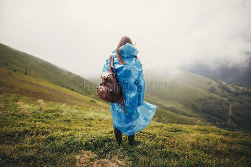 travel and wanderlust concept. traveler hipster girl in blue raincoat with backpack, exploring misty mountains. space for text. royalty free stock photo