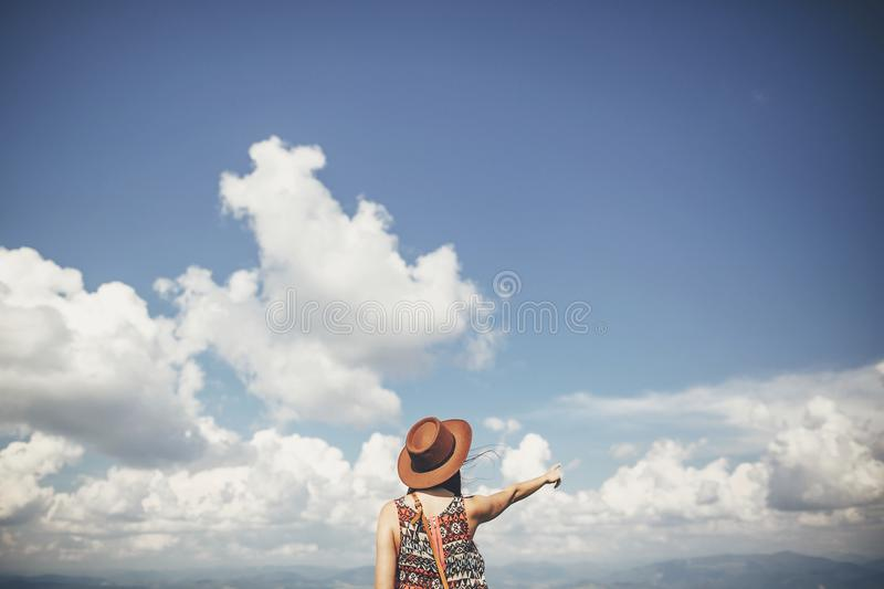 Travel and wanderlust concept. traveler hipster girl in hat stan. Ding on background of clouds and pointing into the sky in sunny mountains. space for text stock photo