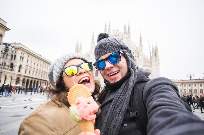 Travel in winter concept - Young and happy tourist making selfie photo in front of the famous Duomo cathedral in Milan stock image